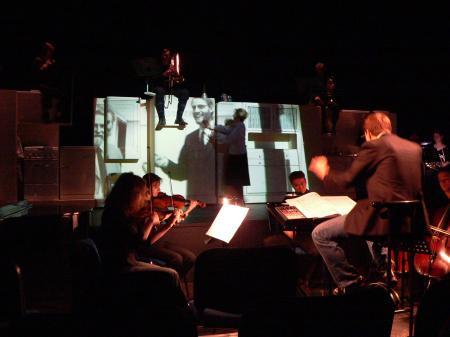 Da es im Next Liberty keinen Orchestergraben gibt, haben wir die Musiker ins Bühnenbild integriert. Die zuerst flache Küchenzeile diente während der Overture als Projektionsfläche für einen Film.