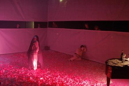 Zuschauer stehen um den abgespannten Raum auf einem Podest, (Gitterplane,innen weiß, außen dunkel) und können durch einen Schlitz zusehen.